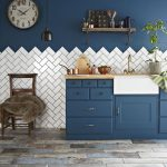 Half Way Parquet Herringbone Tile Half Way Navy Blue Walls Navy Blue Kitchen Cabinets Farmhouse Sink In White Dark Finish Wood Chair Rustic Wood Plank Floors Black Pendant Old Look Clock