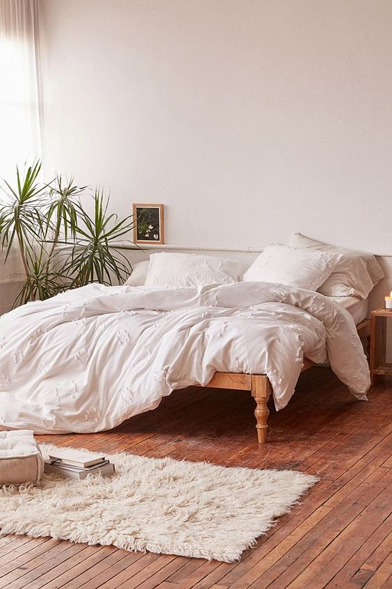 lightweight duvet cover in white white pillows white linen bedspread wooden bed frame white shag rug runner