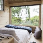 Minimalist Treehouse Bedroom White Bedspread Navy Blue Comforter Light Wood Interior Glass Window