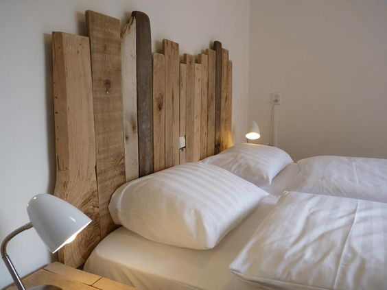modern bedroom with rustic wooden headboard a couple of modern night lamps in white crisp white bedding treatment