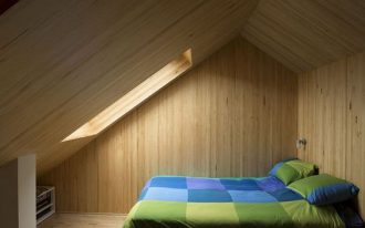 modern cabin style bedroom with green blue bedspread platform bed with under storage wood walls ceilings and floors skylight