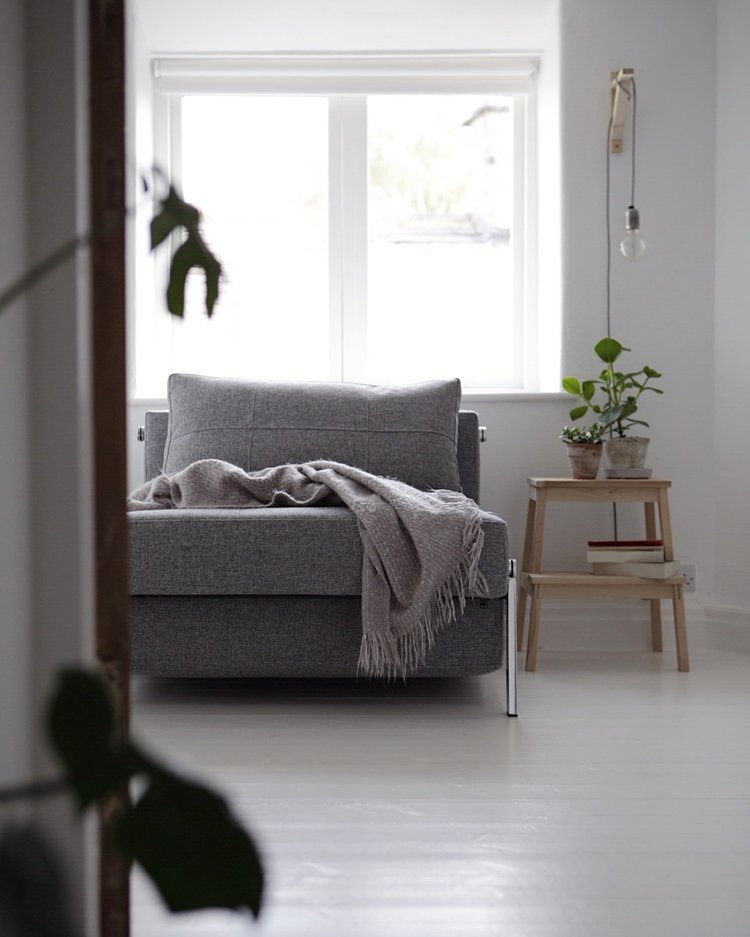 modern gray sofa with gray throw blanket light wood side table with potted greenery crisp white floors and walls