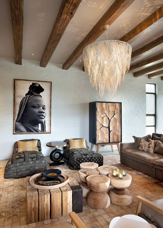 nature inspired living room some tree trunk tables dark sofas with tribal patterns earthy brown sofa huge chandelier with macrame accent huge African woman picture on wall