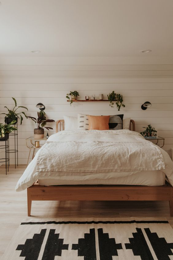 simple modern Boho bedroom wood bed frame white bedding treatment rug with big black geometrical patterns houseplants on planters