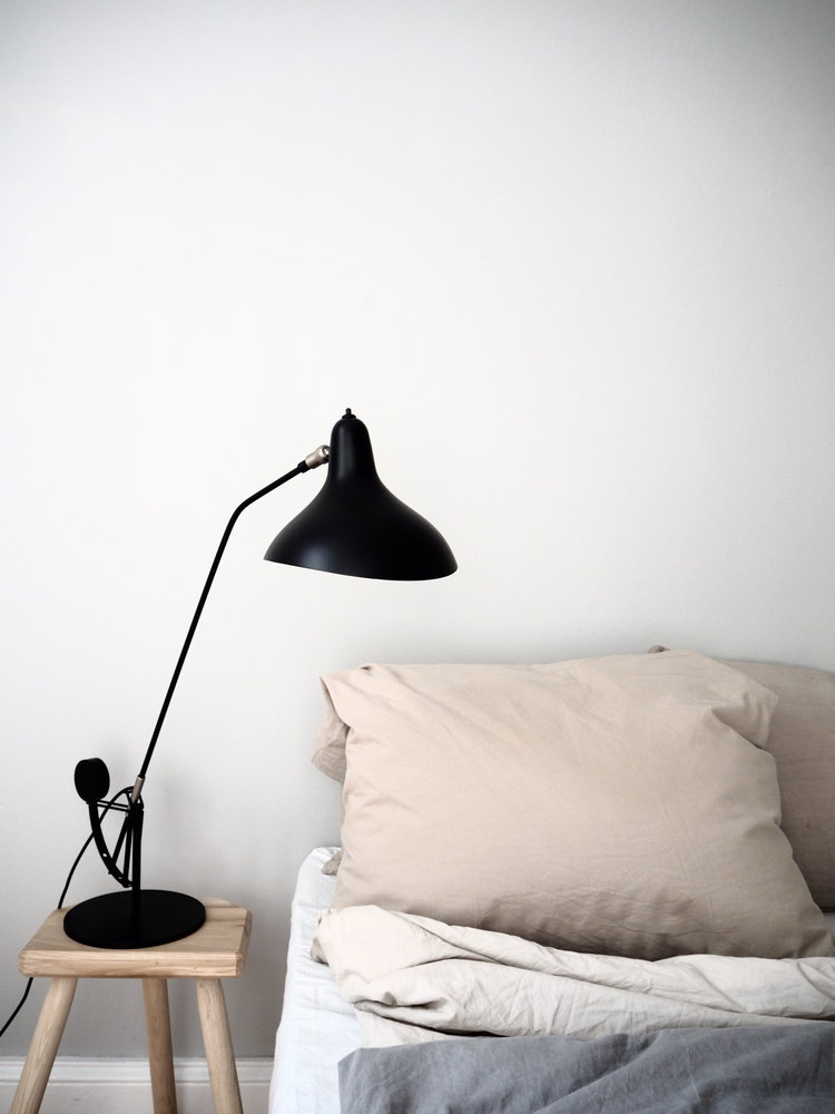 simple yet comfortable bedroom soft and neutral bedding idea light wood bedside table modern black table lamp