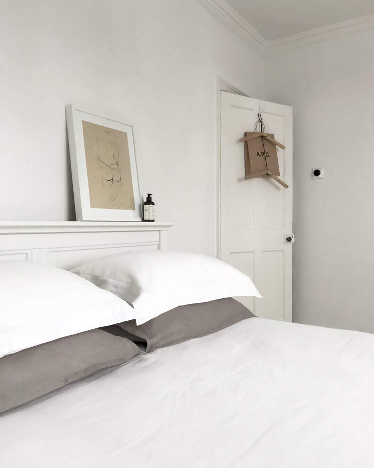 white bed linen white and gray pillows clothes hang behind the door