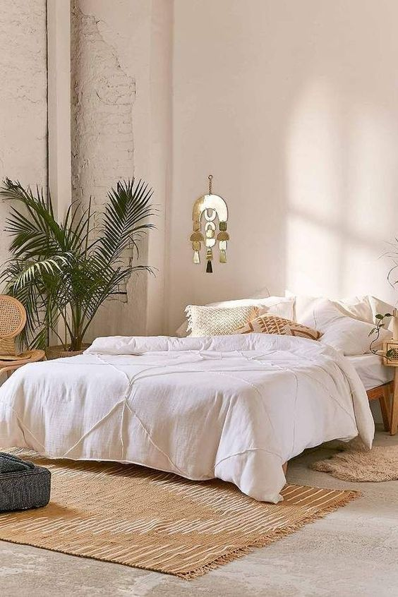 white duvet cover white pillows light brown area rug with fringed trims tropical houseplants metal wall art