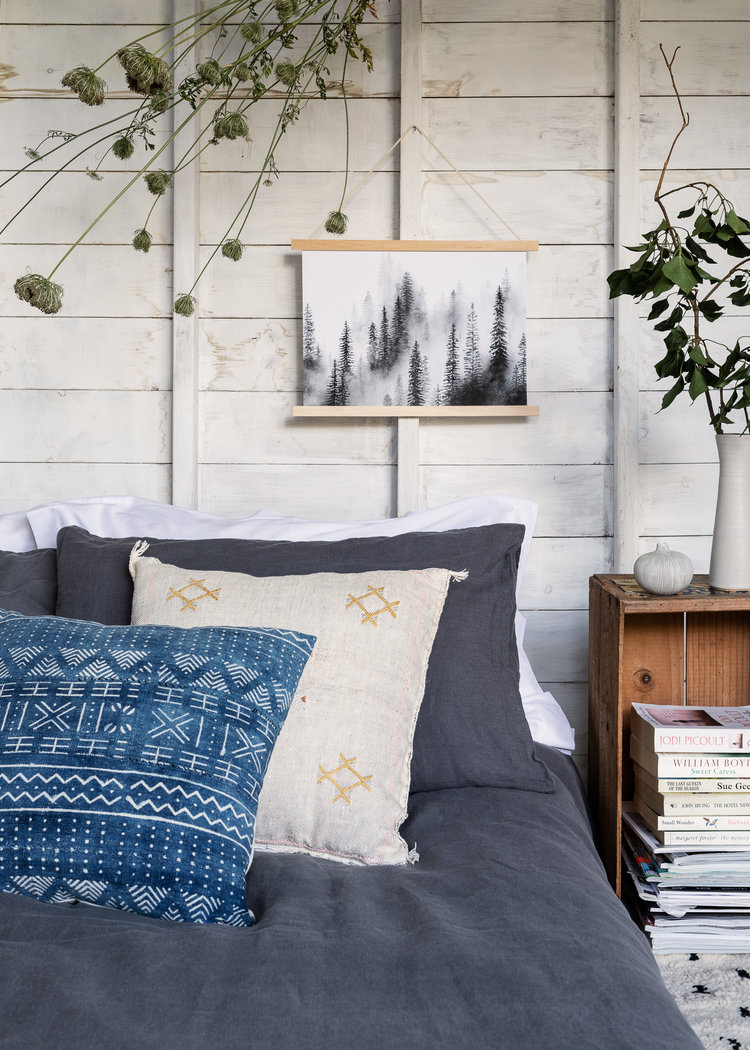 wood plank walls in whitewashed finish wooden bookshelf blue bed linen and pillow