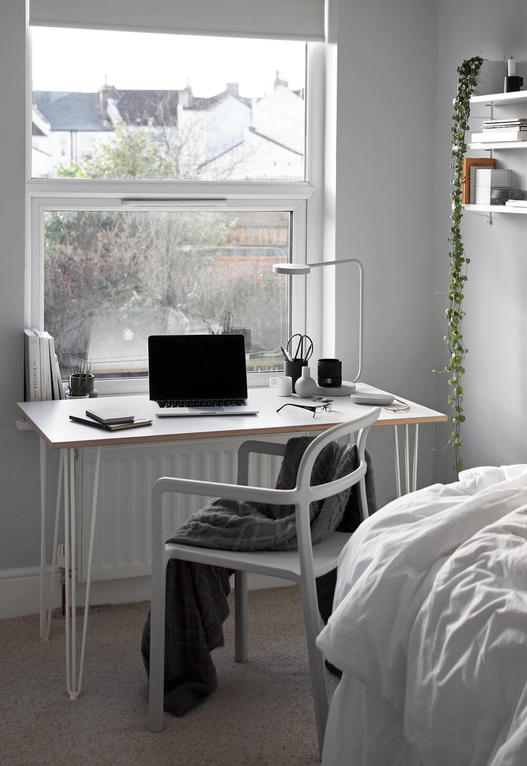 workspace in guest room wood top working table white working chair huge glass window with white trims
