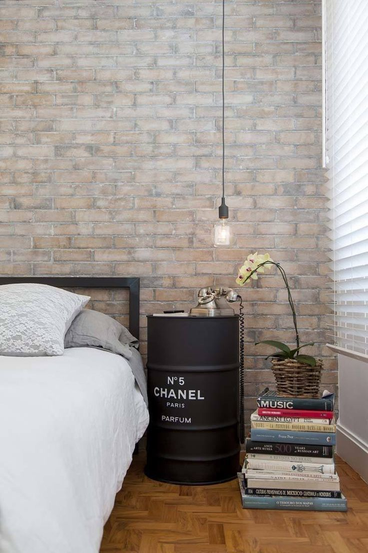 DIY oil drum bedside table in black a pile of books brick wallpapers wood floors