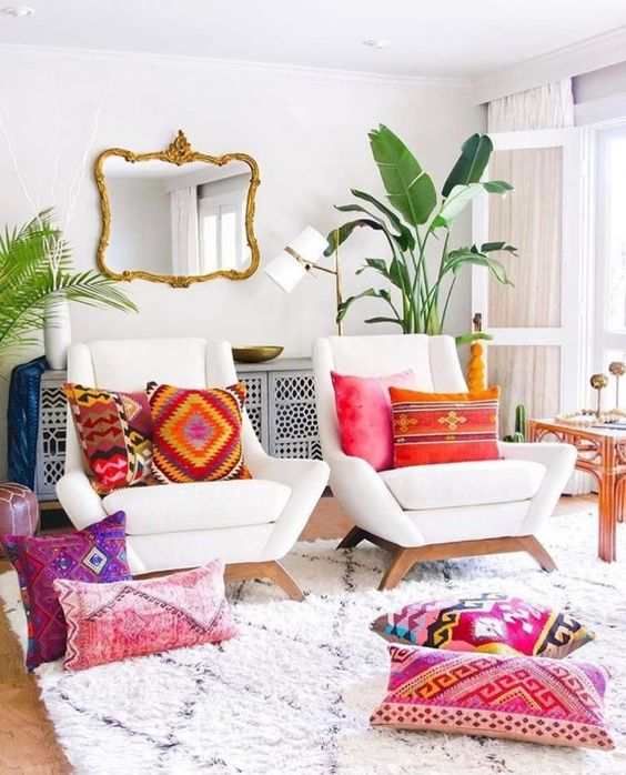 a couple of armchair in white colorful accent pillows and floor pillows wooly area rug with modern motifs tropical houseplants wall decor with artsy gold tone frame