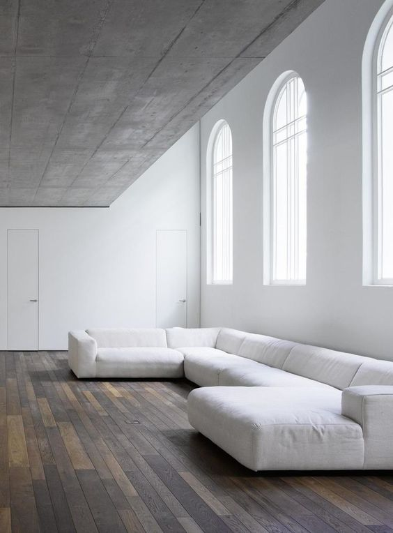 beton ceilings purely white walls modern white modular sofa wood plank floors
