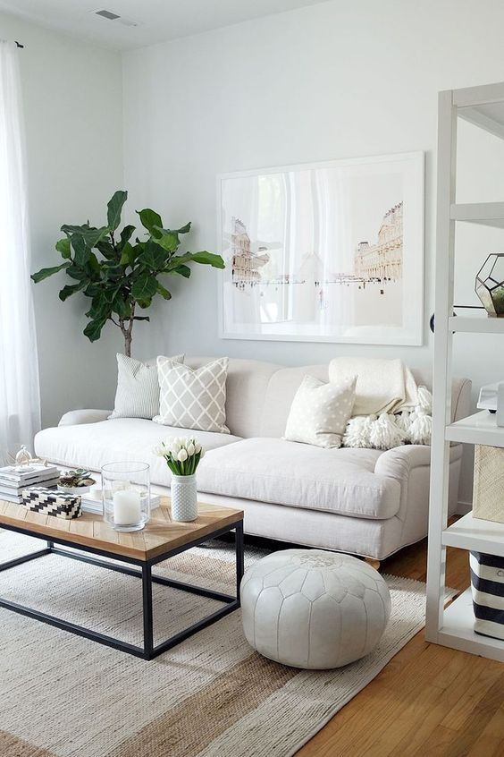 brightly white living room white modular sofa wood top coffee table with black metal frame white Moroccan pouf wood floors modern white area rug potted houseplant