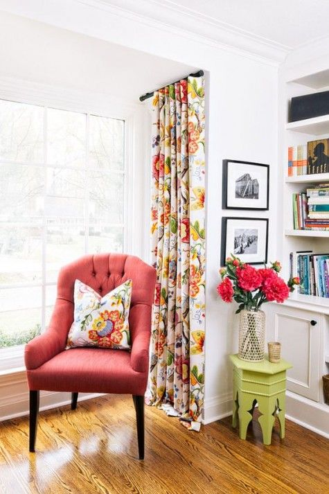 coral armchair with a throw pillow multicolored window curtains green side table