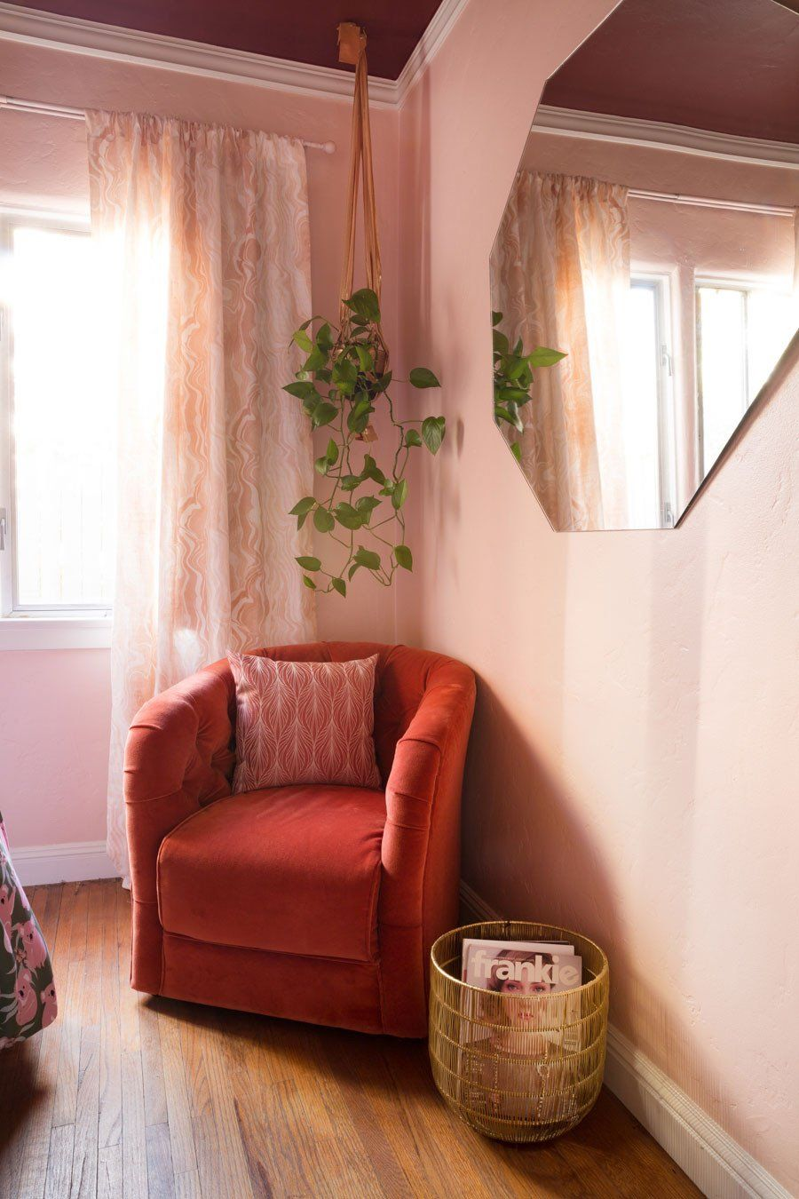 coral armchair with soft pink throw pillow soft pink walls soft pink window curtains wood floors