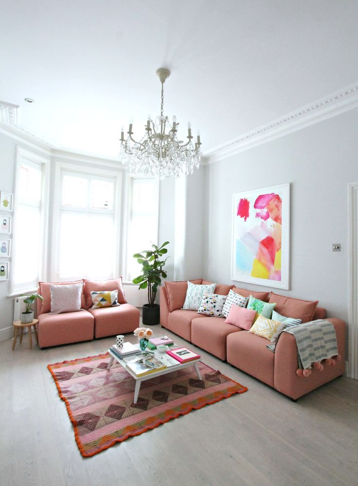 coral pink sofa with lot of throw pillows coral area rug with multicolored patterns white coffee table