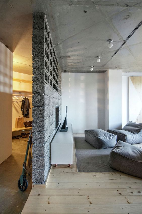 durable and stylish concrete room partition light gray beanbags and cushions light wood plank floors rough concrete ceilings