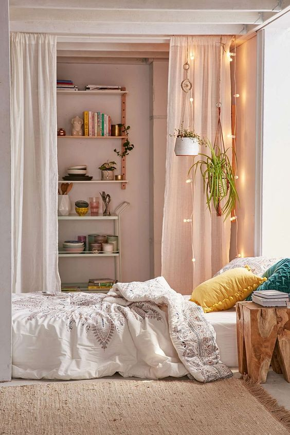 floor bed setting with colorful pillows white bed shirt and white quilt cover dramatic white textile room partition with accent lighting addition and hanging plants
