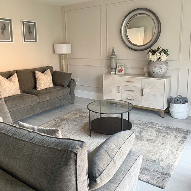 gray dominated living room deep gray sofa with throw pillows velvet area rug in gray whitewashed console table with round wall mirror on its top modern coffee table with round top and under shelf