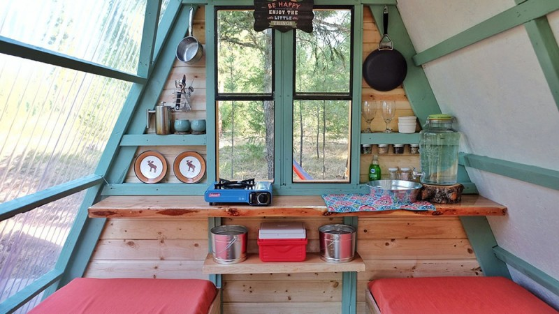 guest cabin's interior consisting of a couple of bed frames floating wood bar table mini shelving units for storage space