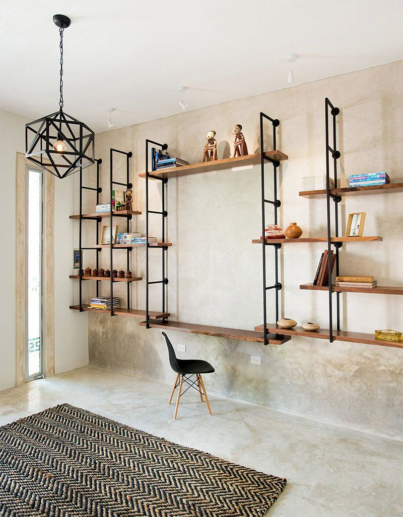 modern industrial loft workspace with industrial piping system for book shelves midcentury modern working chair area rug with geometric patterns
