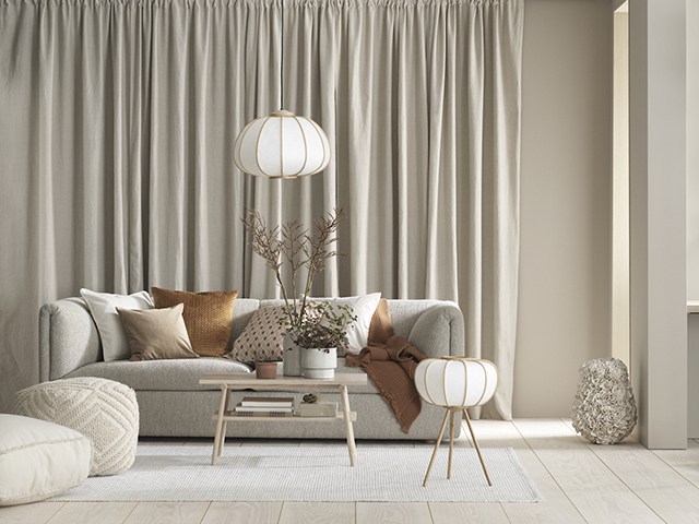 modern sofa in soft gray earthy brown throw pillows white pouffe white area rug lantern like light fixtures with brass accents