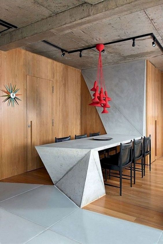 rough concrete ceilings black piping for light fixtures accent chandelier in red wood finish walls and floors smooth concrete finish wall and dining table black dining chairs