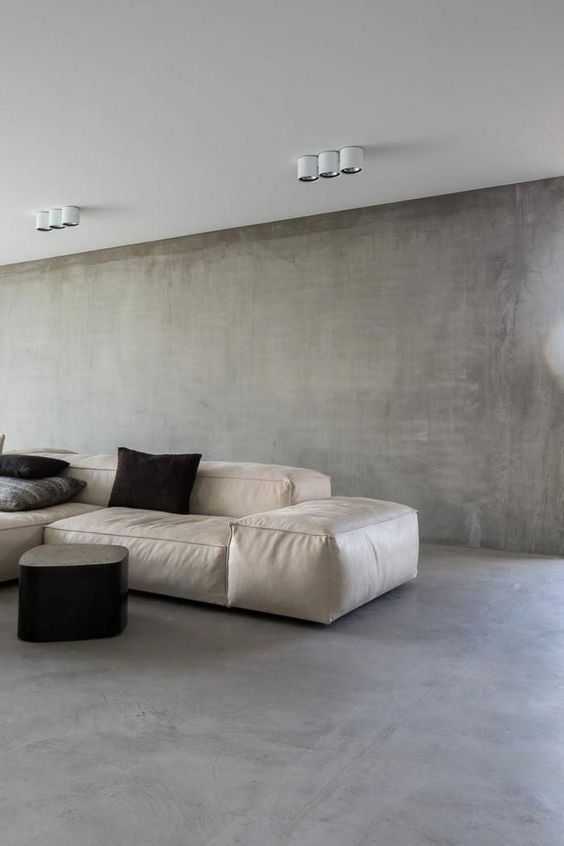 smooth concrete walls and floors contemporary modular sofa in white black accent pillows black coffee table in contemporary style white ceilings with modern lighting fixtures
