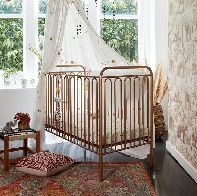tan metal baby crib with railings multicolored area rug a floor pillow low profile table ornate bed curtains