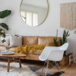 Texile Area Rug White Shag Rug Wood Coffee Table Light Brown Leather Sofa Mustard Throw Blanket Light Wood Floors White Rocking Chair Large Round Wall Mirror With Brass Frame