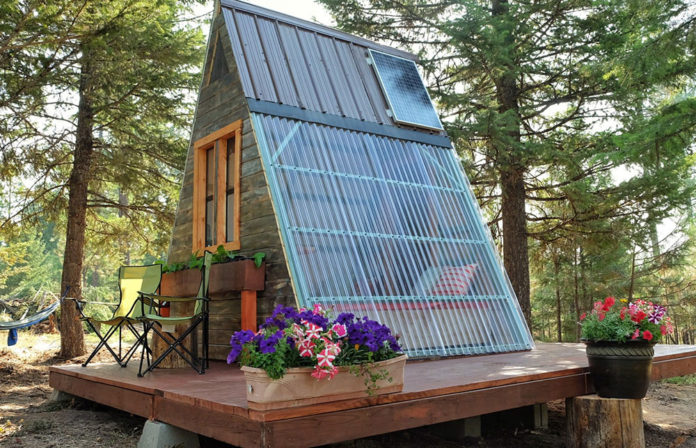tiny guest cabin exterior with small porch and solar panel