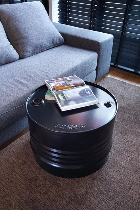 vividly black gallon drum coffee table with masculine look
