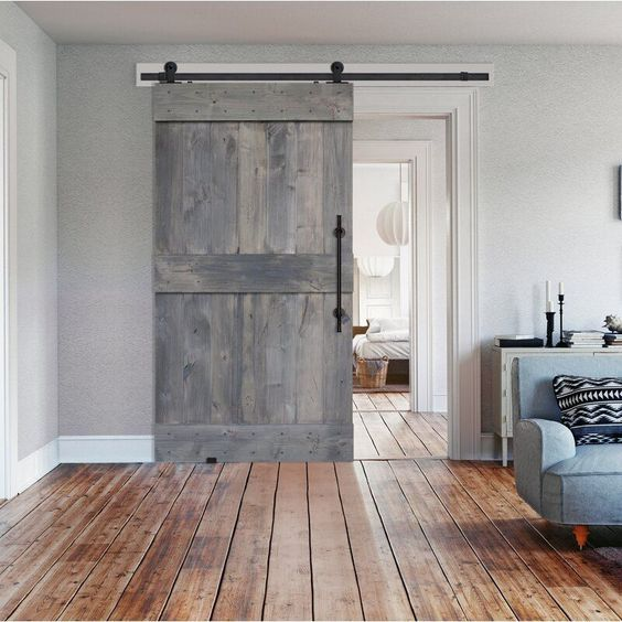 washed wood finish barn door wood plank floors midcentury modern sofa in gray