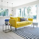 Yellow Sofa In Midcentury Modern Style Striped Black White Area Rug Modern Side Table With Glass Top