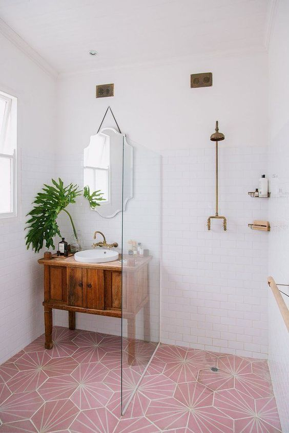Scandinavian bathroom with hard wood bathroom vanity white deep sink clear glass shower partition walk in shower pink tile floors with white patterns white subway tile walls