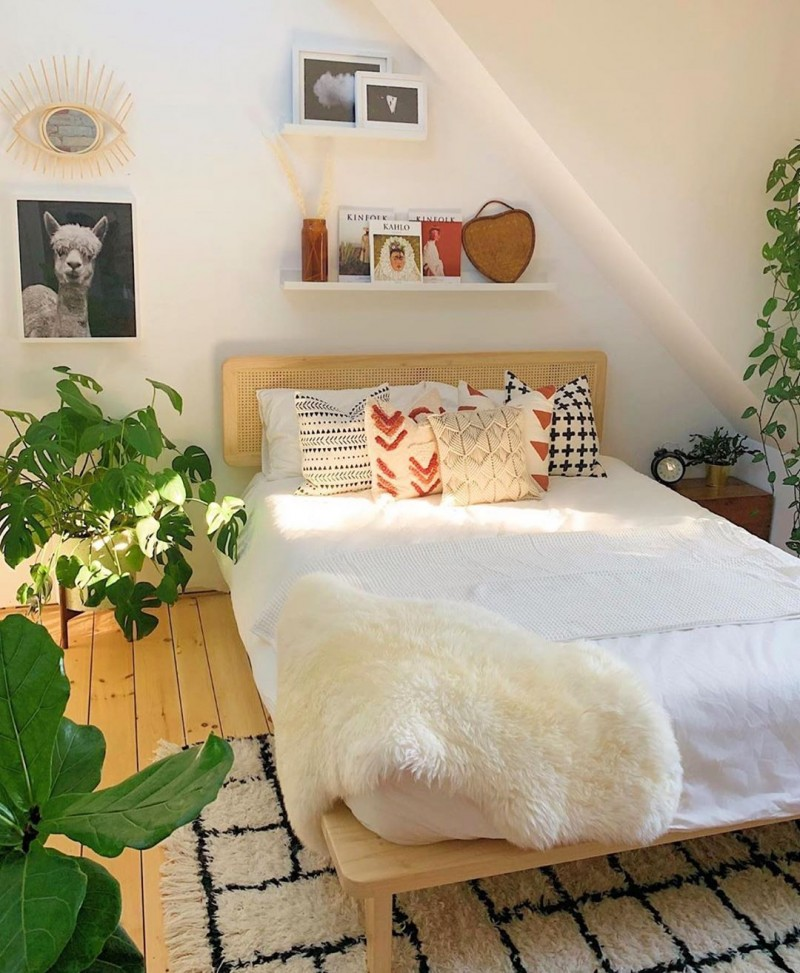 bright bedroom design with slanted wall and ceiling white bedding treatment wood plank floors modern area rug in black white some greenery