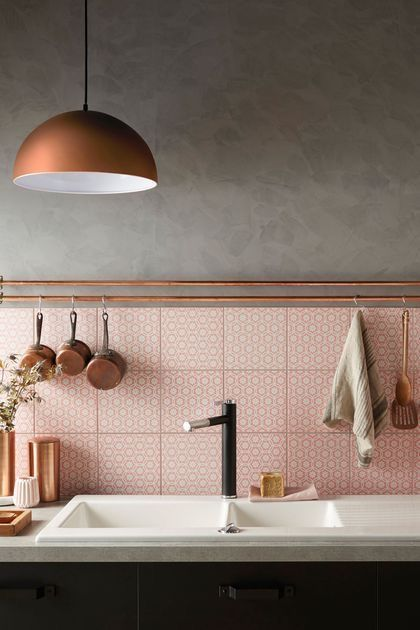 concrete walls soft pink tile backsplash with texture copper piping and copper cooking tools white sink