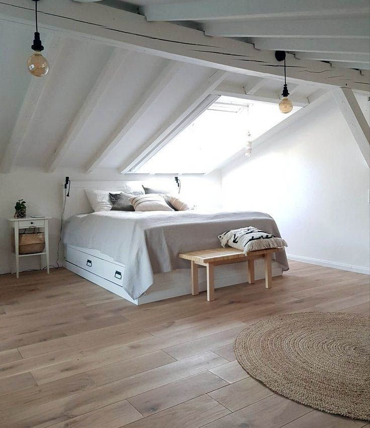 cool white attic bedroom white bed frame with under storage white bedside table wood bench bed flat woven rug in round shape skylight light wood floors