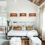 Daybed With White Cushion And Worn Out Headboard A Couple Of Footrest Wall Light Fixtures With Oversized Lampshades Dramatic White Draperies Reclaimed Wood Ceilings