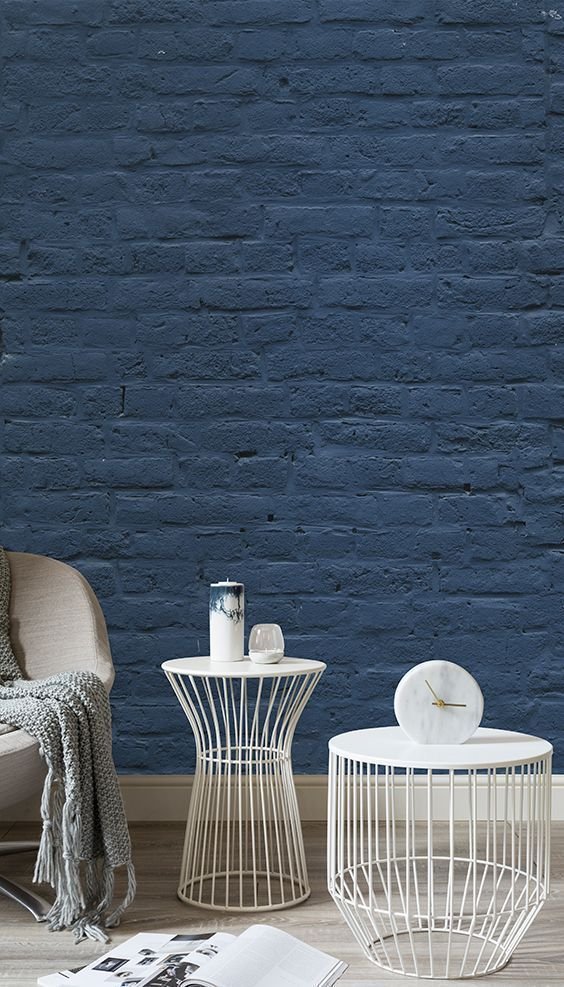 deep blue brick walls white round top side tables with cage like base light gray accent chair with gray knitted blanket