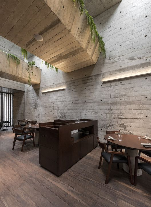 dining space with gardens on top wooden floors concrete walls dark wood dining furniture