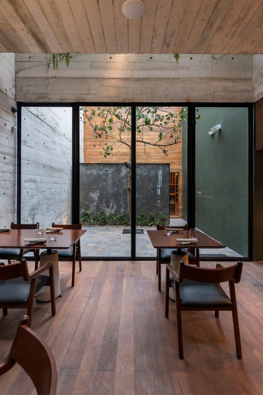 dining space with modern dining furniture made of dark wood dark wood floors glass door and windows with black frames greenery with concrete wall background