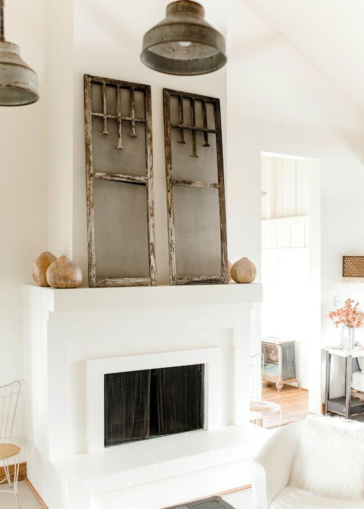 fireplace with white finish concrete mantel worn out window shutter as the ornament