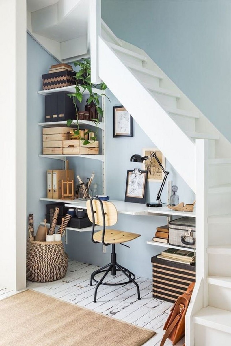 home office in the basement working table under the staircase modern industrial working chair uncluttered shelving unit whitewashed wood floors