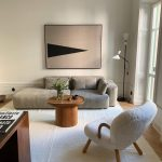 Light Gray Sectional Sofa Round Top Wood Coffee Table Wooly Armchair With Wood Frame White Area Rug Modern Wall Art Floor Lamp