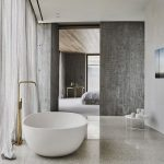 Minimalist Master Bathroom With Brass Stand Faucet Modern White Tub Beton Walls Dramatic Gray Drapery