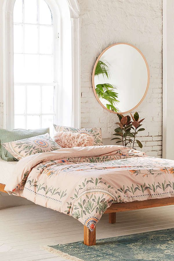 modern Boho bedroom design with floral bedding set wood bed frame white brick walls  round wall mirror with wood frame