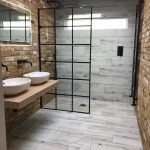 Modern Industrial Bathroom Design With Glass Room Partition With Black Metal Trims Stone Brick Shaped Walls Light Tile Walls And Floors Wood Bathroom Vanity With White Sinks
