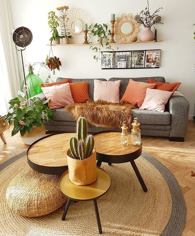 modern living room with boho touch gray sofa with tan pink throw pillows round top coffee tables with angled legs round shaped flat woven area rug some greenery