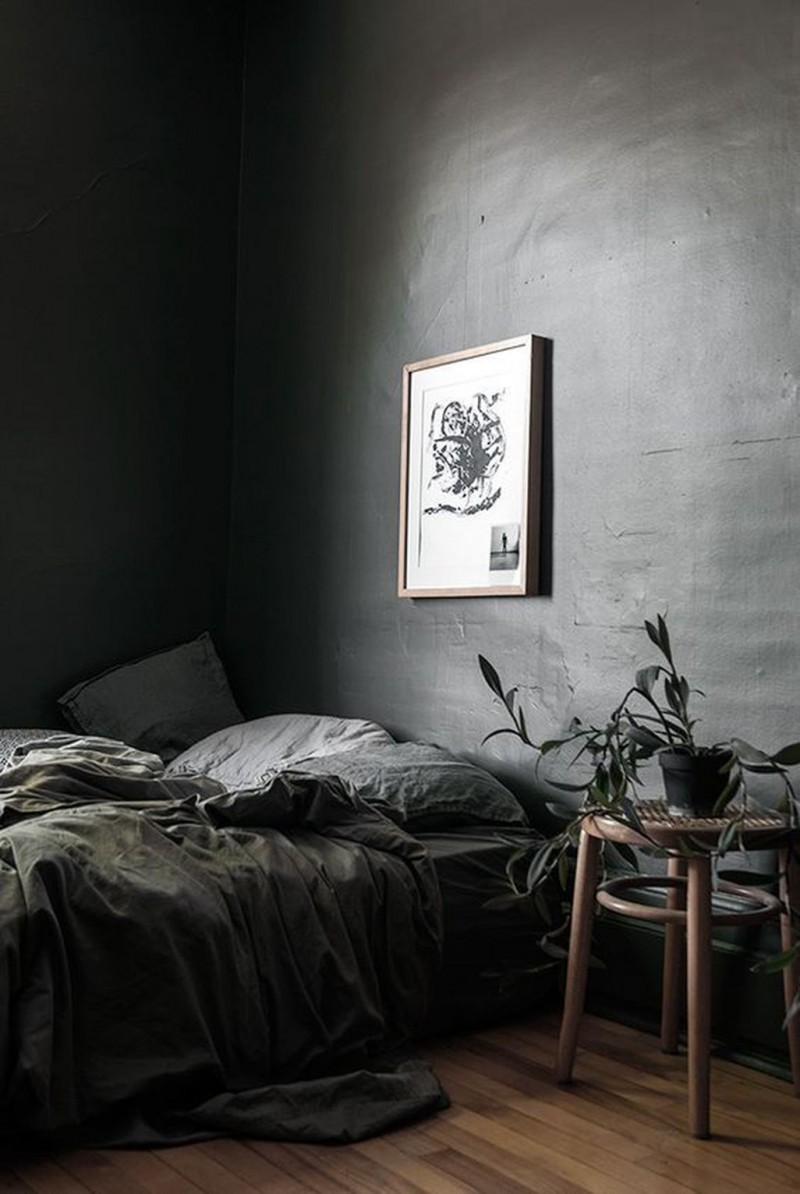 simple minimalist bedroom design in black black walls black bed linen and pillow wood floors round top stool for greenery